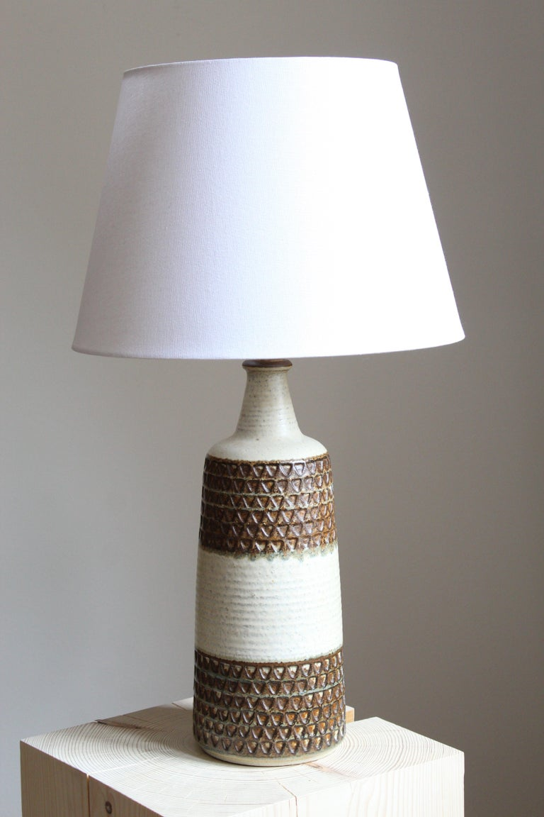 A large table lamp produced by Søholm Keramik, located on the island of Bornholm in Denmark. Features a highly artistic glazed decor.   Sold without lampshade. Stated dimensions exclude the lampshade.  Other designers of the period include Axel