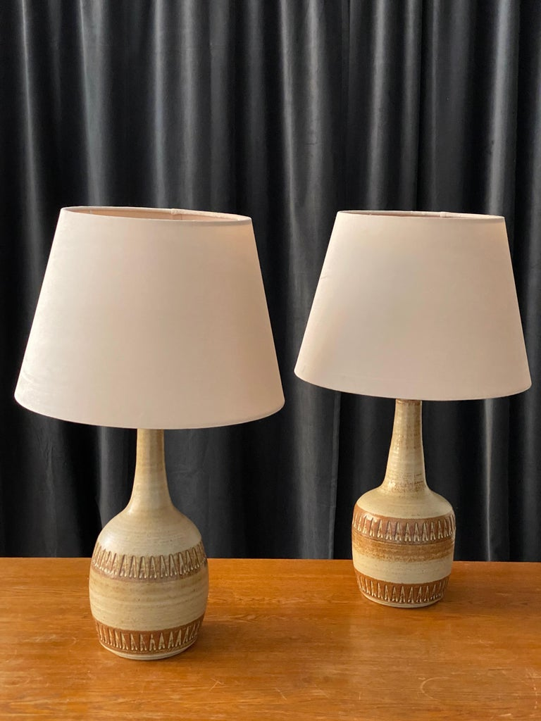 A pair of table lamps produced by Søholm Keramik, located on the island of Bornholm in Denmark. In a highly artistic brown / grey / beige glaze. The lamps are not identical, adding to the rustic expression of the pair. 