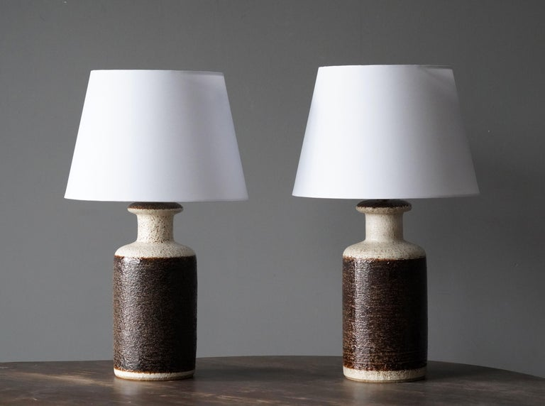 A pair of table lamps produced by Søholm Keramik, located on the island of Bornholm in Denmark. In a highly artistic brown / beige rake-style glaze. The lamps are not identical, adding to the rustic expression of the pair. 