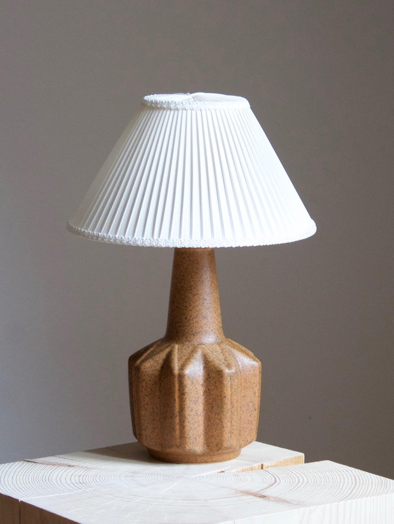 A large table lamp produced by Søholm Keramik, located on the island of Bornholm in Denmark. Features a highly artistic glazed and incised decor.   Sold without lampshade. Stated dimensions exclude the lampshade.  Other designers of the period