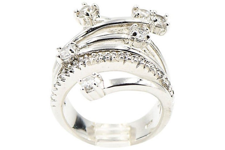 This ring is reminiscent of shooting stars or fireworks. The sterling silver ring has branches that crossover one another with prong set crystals at the end of each branch. There is also a singular band that just has crystals going across. The back