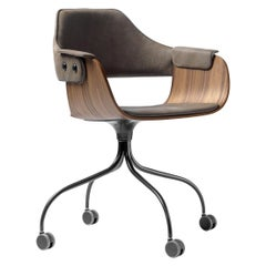 Upholstered desk chair in walnut and leather on casters.