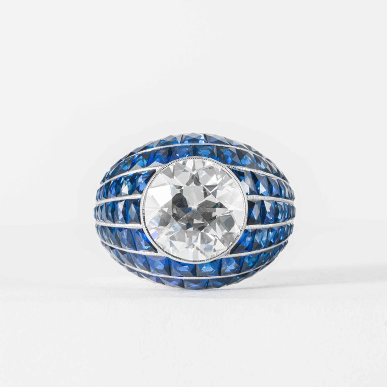 This elegant and classic diamond ring is offered by Shreve, Crump & Low. This 5.03 carat GIA certified J VS2 old European cut diamond is custom set in a handcrafted Shreve, Crump & Low blue sapphire Bombe style ring. Set with 7.73 carats of square