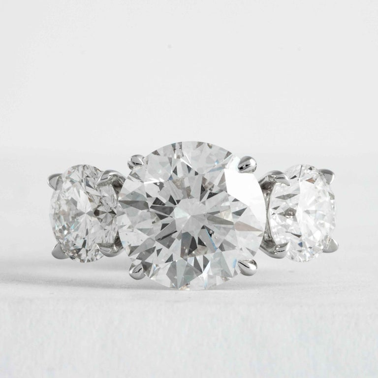 This elegant and classic diamond ring is offered by Shreve, Crump & Low. This 3.51 carat H SI1 round brilliant cut diamond is custom set in a handcrafted Shreve, Crump & Low platinum 3-stone ring. The 3.51 carat center diamond is accented by two