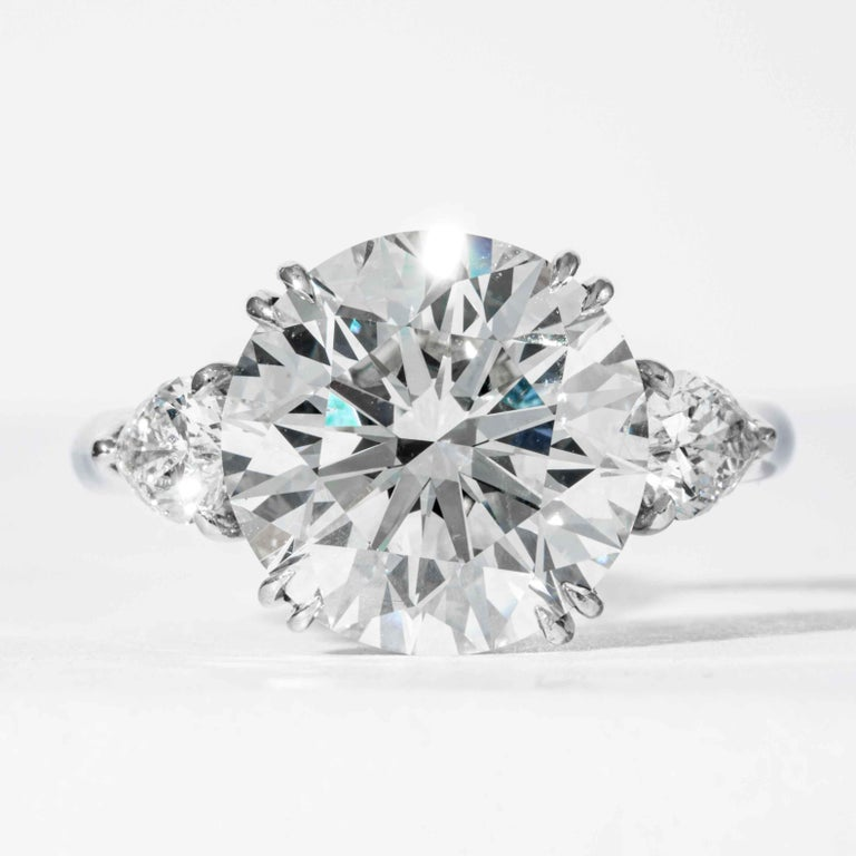 This diamond ring is offer by Shreve, Crump & Low.  This 5.90 carat GIA certified K VS2 round brilliant cut triple excellent diamond measuring 11.44-11.55 X 7.2 mm is custom set in a handcrafted Shreve, Crump & Low platinum 3-stone ring.  The 5.90