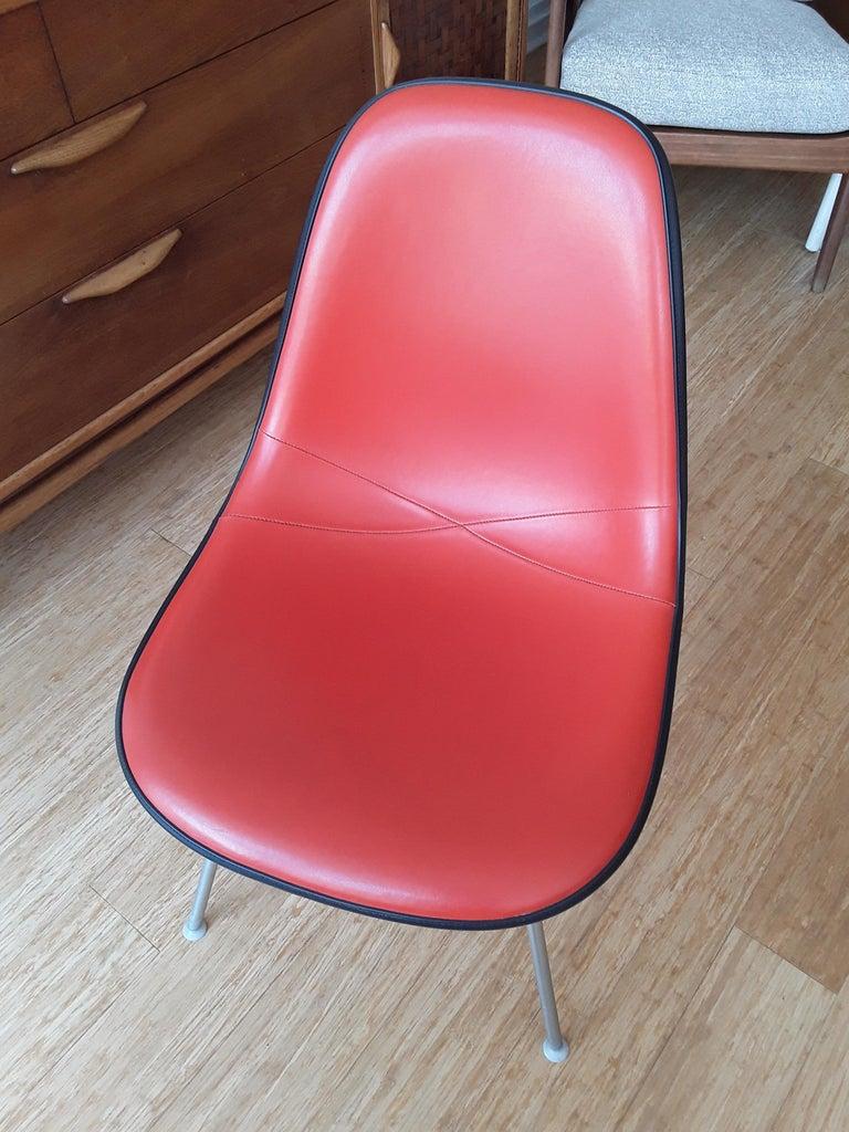 Eames fiberglass shell chair. Upholstered in orange Naugahyde.