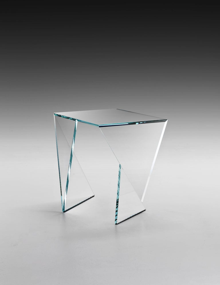 The side table 'Origami Calcio' is made of extra-clear glass. Side table dimension: L55 W40 H50cm. The inspiration for origami came from the observation of a simple piece of paper which, being folded a few times according to an antique Japanese