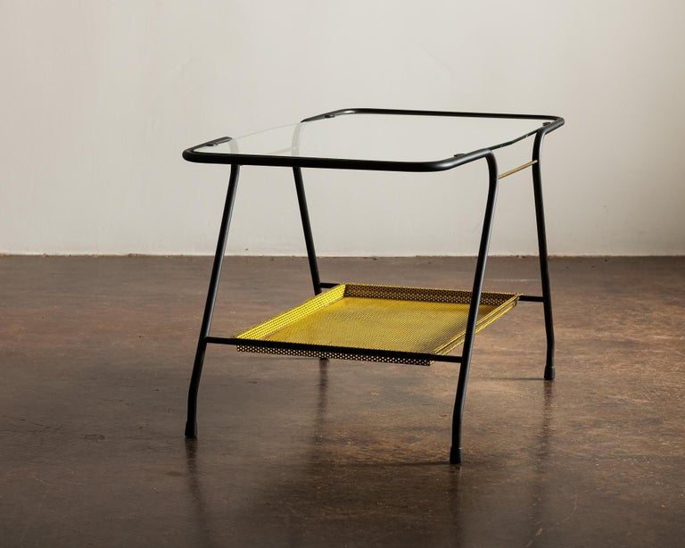 French side table in lacquered tubular metal with perforated bottom shelf, brass accents and top in glass.
