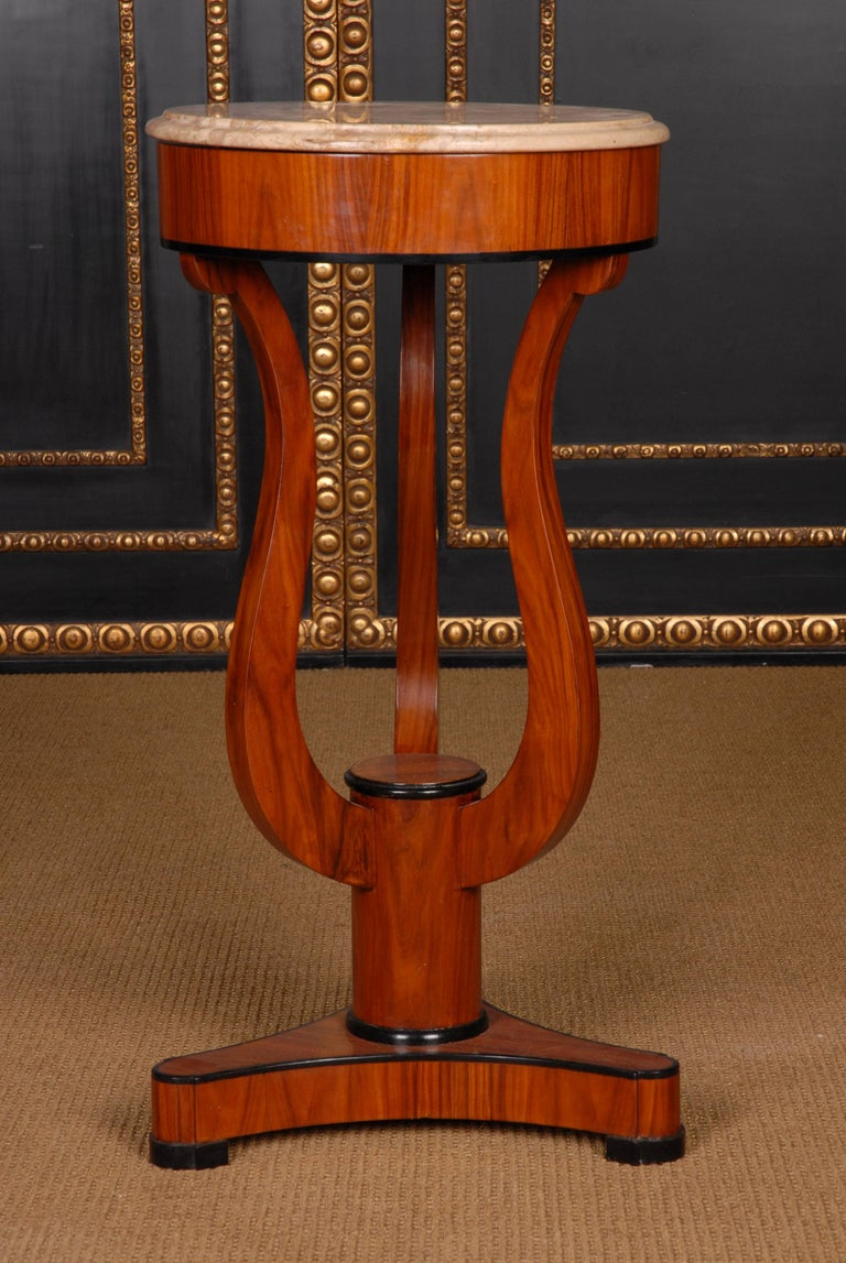 Exotic rosewood on solid wood and partly boned. Round sheet with black-and-white solid marble slab, oversized frame and lyre-shaped curly legs on three-sided base plate and disc feet. This form corresponds to the Viennese Biedermeier and is