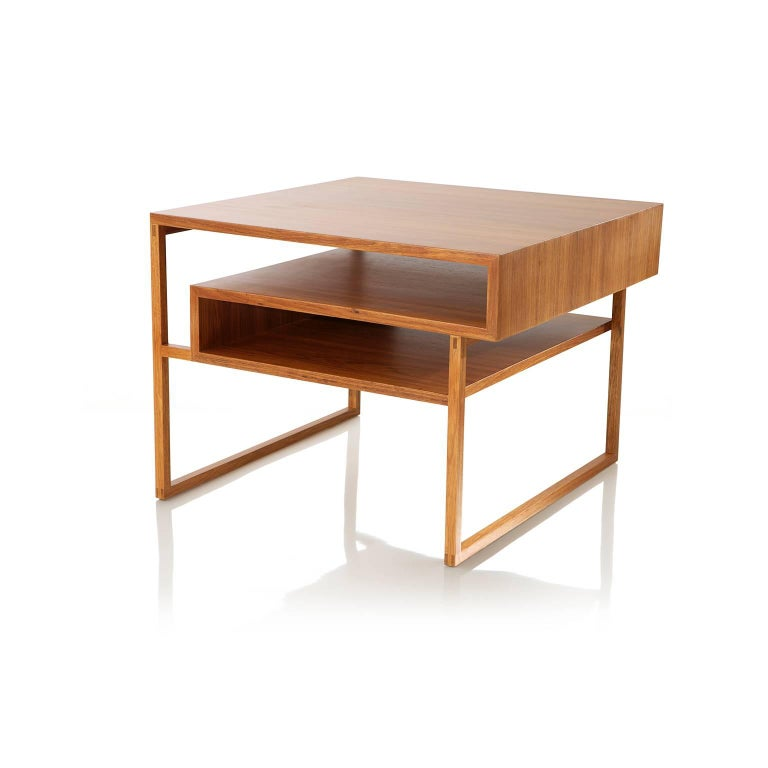The side table Mínim can be used in living room, library, reception, office, entrance hall, bedrooms, entertainment room. The base is made in solid Brazilian wood Freijó with traditional joint techniques. The tabletop is veneered with natural wood.