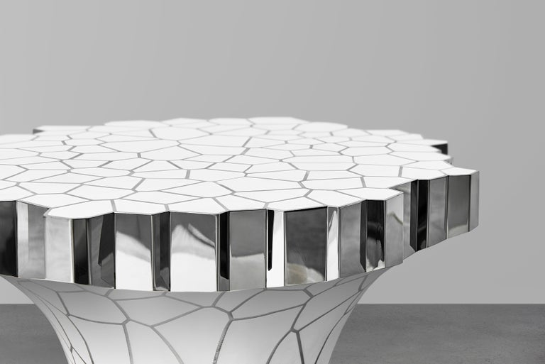 The collection consists of a chair, a side table, a writing desk, a round coffee table, a console and a lounge chair. All the work in the collection will be composed of polished stainless steel with white enamel surfaces. Each piece consists of a