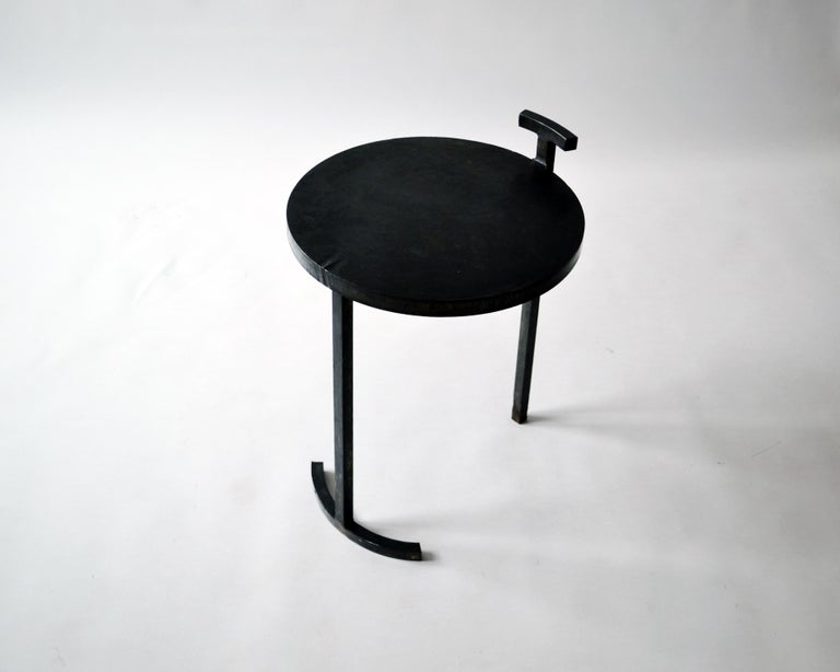 Side table no. 1 - JM Szymanski  Dimensions: H 53.3 cm x Dm 40.64 cm Materials: Blackened and waxed steel.  These side tables are made from cast blackened and waxed steel. A uniquely designed frame allows a 1 inch thick, cast steel, circular top to