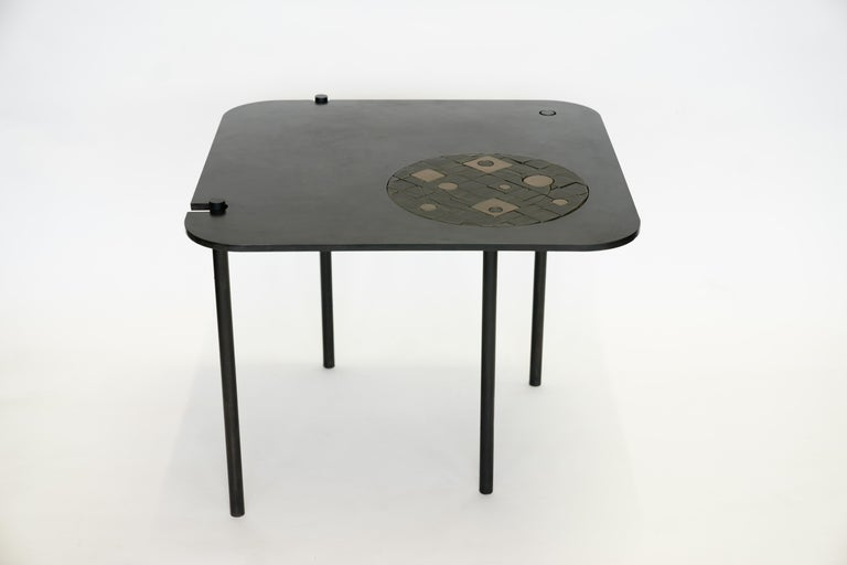 """Side table no. 12 by JM Szymanski Dimensions: L 28"""" x W 28"""" x H 21"""" Materials: Blackened waxed steel  This table is a special collaboration with ceramicist, Eric Monin. A unique ceramic puzzle is inset into the blackened steel frame.  Jake"""