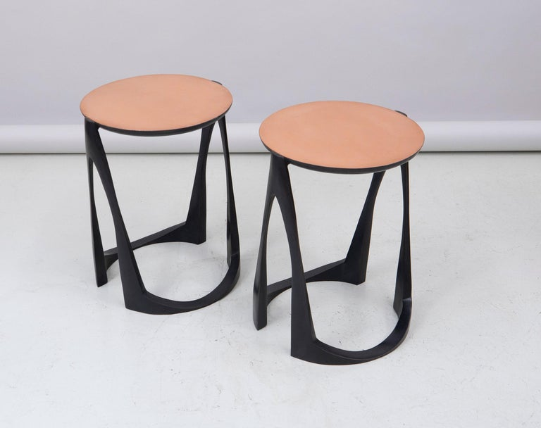 A pair of side tables in bronze with base in black patina and a top in natural bronze.