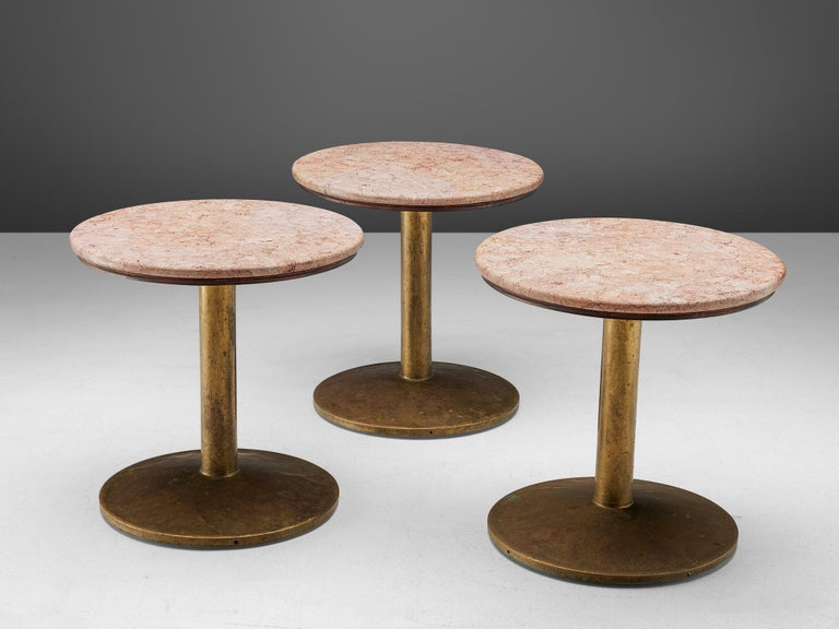 Brass dining tables with rose marble top, France, 1960s.  A circular pedestal table in rose marble with a brass foot.The table has a beautiful contrast between the rustic brass base and the refined marble top. With their modest size, these tables