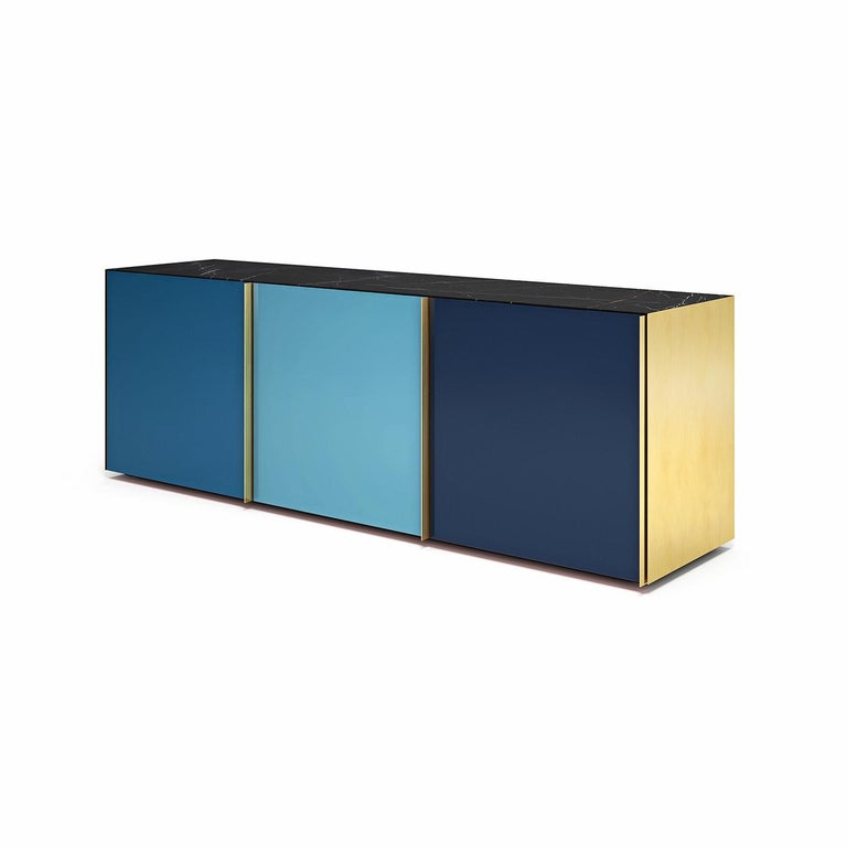 This wooden sideboard will be a statement piece in any modern home in part thanks to the sophisticated, back-paint technique gracing the glass doors in intense tones of blue. Fitted with three doors that open to reveal a spacious interior organized