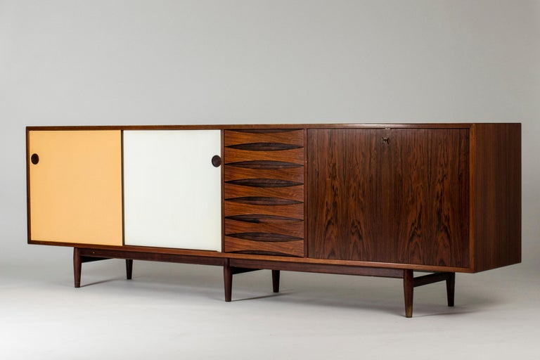 Striking rosewood sideboard by Arne Vodder, where yellow and white panel doors contrast with the cleanly sculpted drawers in the middle and the flaming rosewood veneer on the flap door on the left. The back of the sideboard is made with rosewood
