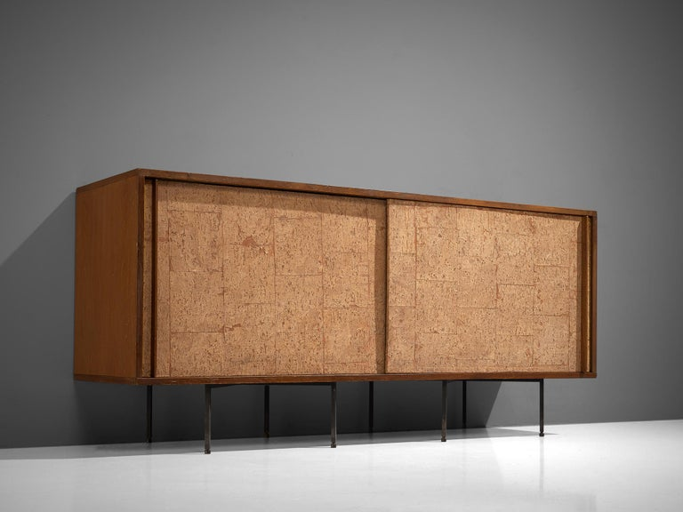 Campo & Graffi, sideboard, wood, cork and metal, Italy, 1960s  This small credenza is executed with two sliding doors executed in cork with wooden handles that run all the way from the top to the bottom of the doors. The credenza is placed on