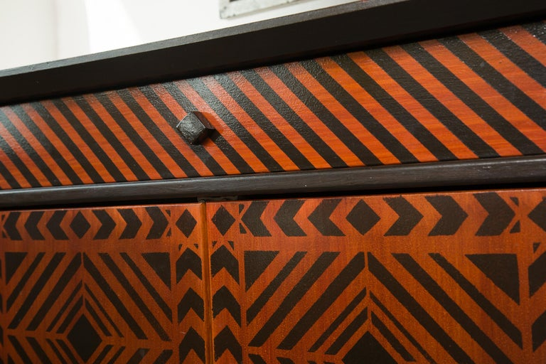 This stunning show-stopper is a custom designed credenza or sideboard., originally commissioned by fashion designer, Arnold Scassi. The entire cabinet is decorated overall in a brown and black geometric pattern, creating an op art motif. The
