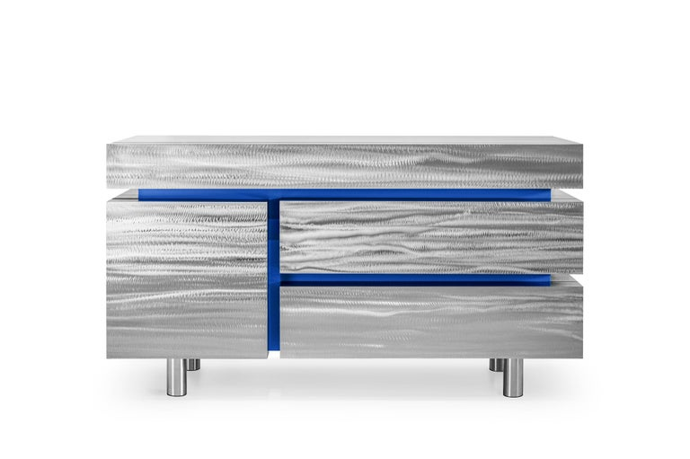 The metal sideboard has four drawers and is contemporary, massive, and elegant at the same time. This is a kind of understanding of modernist aesthetics, where the subject consists of a group of simple geometric figures. The graphic drawing of the