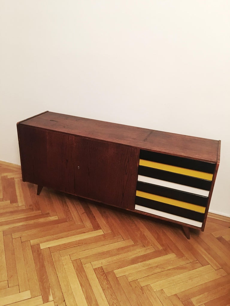 Original vintage sideboard with two doors and the side drawers in black and yellow and grey-blue combination. Type U-460, manufactured in the 1960s by Interier Praha, designed by Jiri Jiroutek. Wooden construction and wooden drawers.  Dimensions: