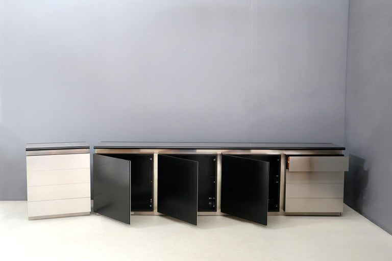 Cabinet with modular elements with spacers and doors covered in stainless steel. Production Acerbis, 1971. The sideboard is made of lacquered open pore Revere wood. With 4 openable wooden doors and functional drawers on its sides. One side of the