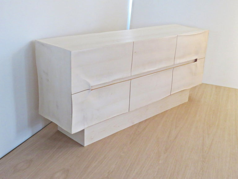 These sideboards are made by hand in organic design. The furniture is very sculptural but modern, through the surfaces with wrinkles and bumps creates a play with light and shadow. The grip section is integrated and incorporated into the