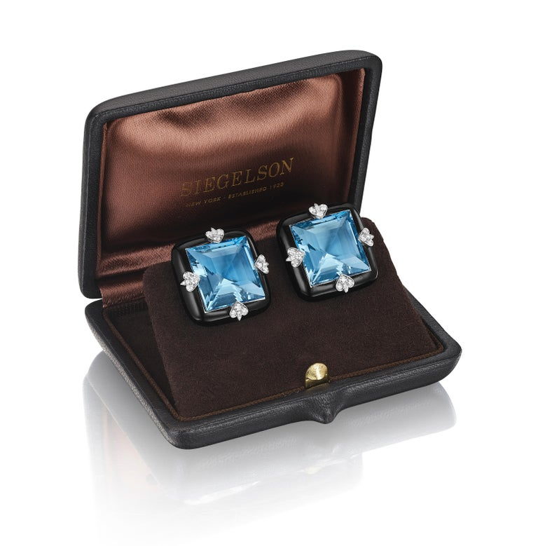 A pair of ear clips, each centering a step-cut aquamarine framed in black ceramic, the aquamarines accented by diamonds set in white gold spades; mounted in 18-karat white gold • 2 step-cut aquamarines, weighing 12.8 and 13.0 carats • 40 round