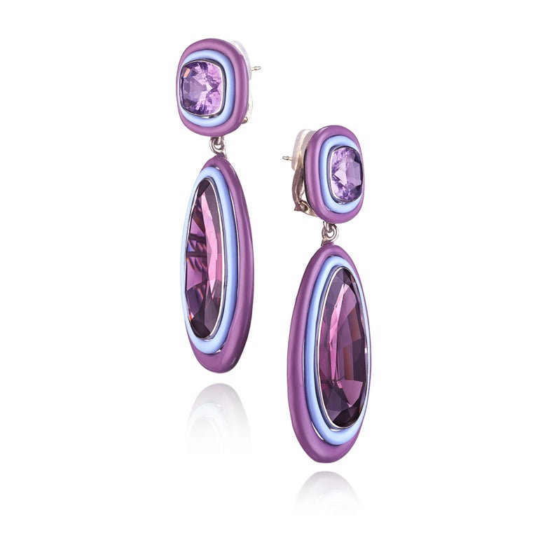 A pair of ear clips, each featuring a pear-shaped spinel framed in varying shades of purple-colored ceramic, suspended from a similarly framed cushion-shape amethyst; mounted in white gold • 2 pear-shaped spinels, weighing 36.72 and 35.80 carats • 2