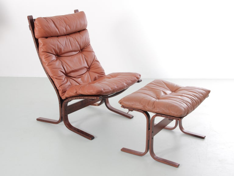 Siesta chair high back and ottoman by Ingmar Relling. Cognac leather. Excellent original condition.