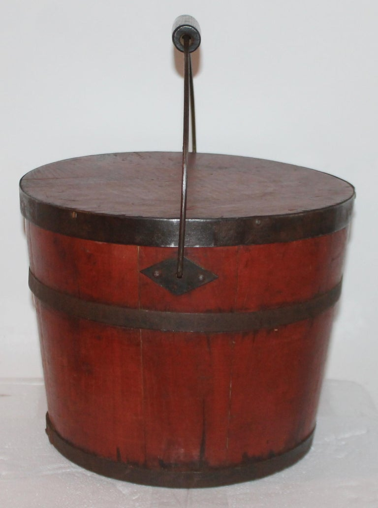 This fantastic 19Th century shaker bucket with original lid with red painted stain surface. This Fine little gem is in great as found condition. Very strong in sturdy condition. It is signed: N.F.SHAKERS -ENFIELD, N.H. on the base.