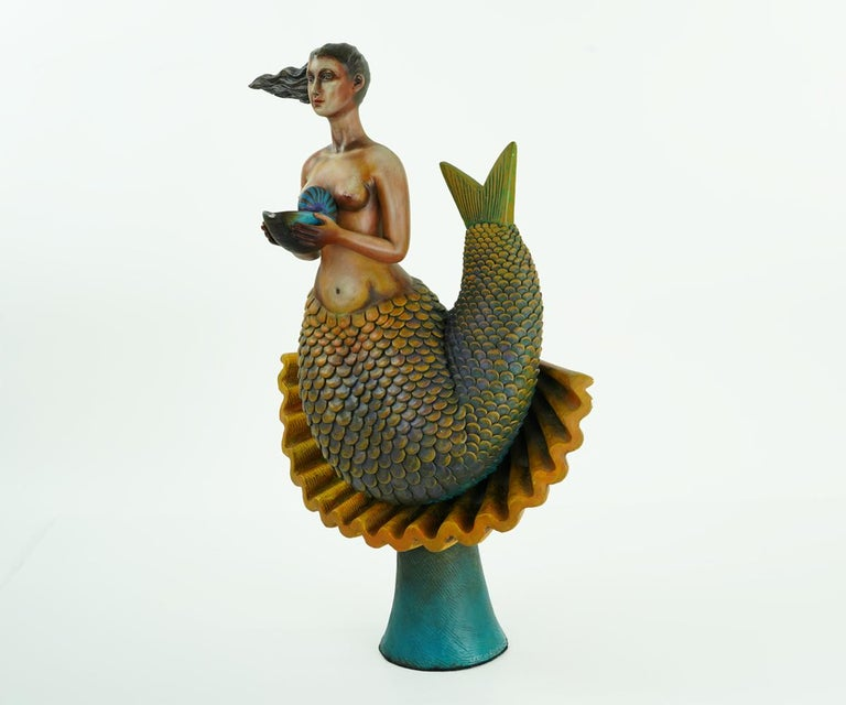 Mermaids were one of Sergio Bustamante's favorite and most popular subjects and this is one of his most collectible pieces as a result. The mermaid rests upon a shell base mounted on a dark turquoise stand and is holding a smaller shell in her arms