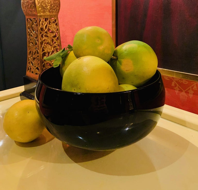 A spectacular Correia Art Glass bowl - large, round and simple, yet the perfect compliment to any table. The small foot, also simple and elegant.  Standing alone or as a piece of art, the subtle Aubergine color looks black to the eye, however,