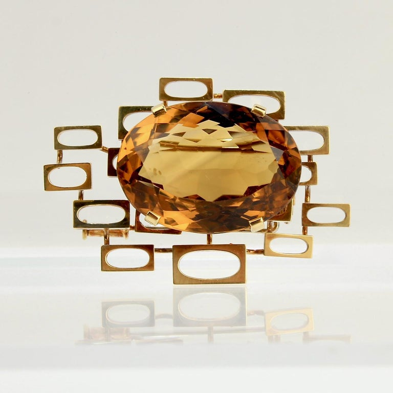 A very fine signed mid-century 18k gold & citrine brooch or scarf pin.  Set with a large oval cut citrine gemstone on a rectangular matrix-like platform.  Made by the Swiss Goldsmith Eric Pickler of Geneva, Switzerland. Pickler was a noted craftsman