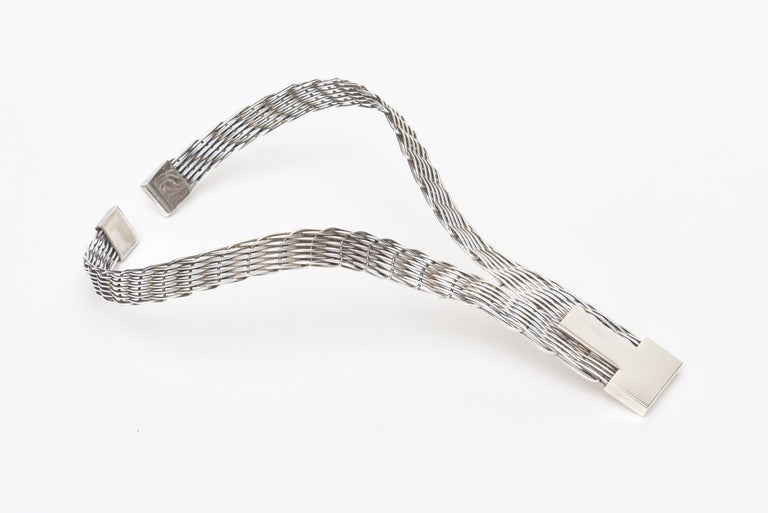 This lovely french necklace is silver-plate and is signed J.P. Coutrel. The weave of silver-plate is textural. It is from the 80's. It rests on the high point of the back of the neck and comes down in a V pattern. Very flattering on. It takes a