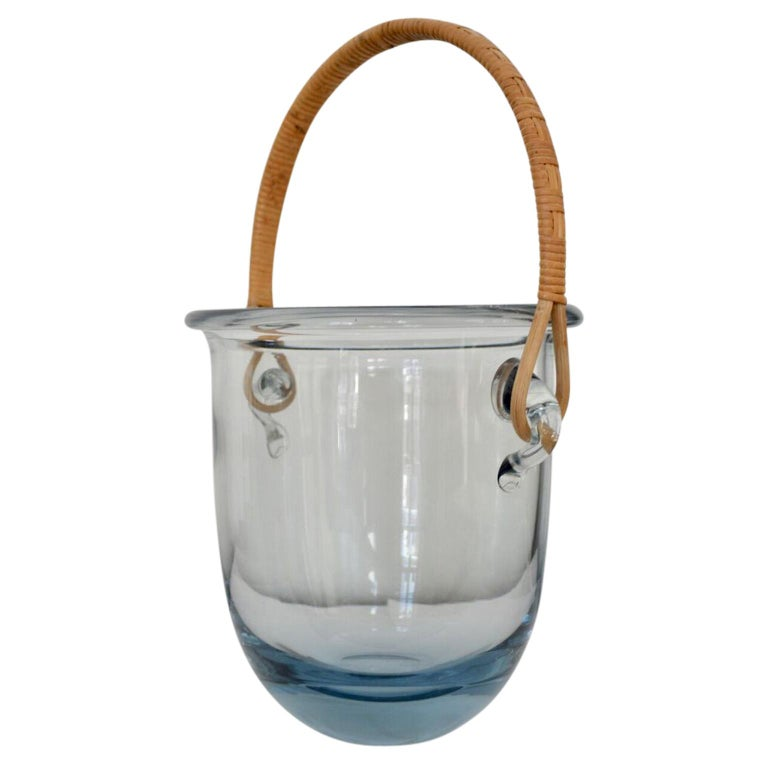 This large ice bucket is probably by Jacob E. Bang, and manufactured by Holmegaard in Denmark. It has a rattan handle and is signed, but not very easy to read.