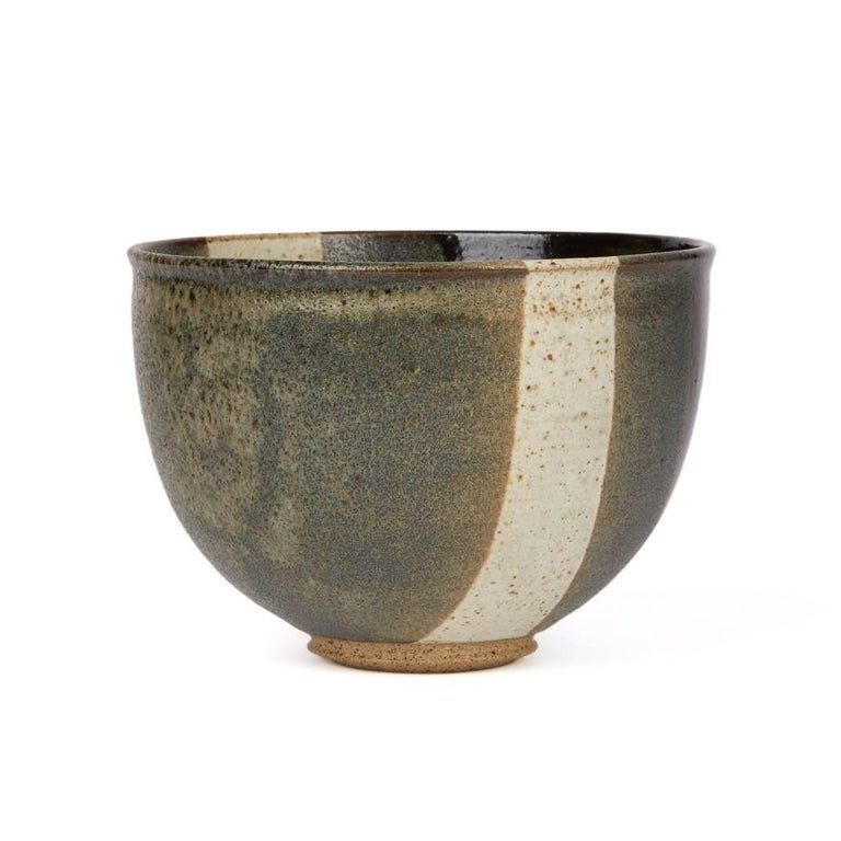 A very stylish rounded Studio Pottery bowl of simple form standing raised on a narrow rounded unglazed foot decorated in banded sections of grey, white and black glazes with a speckled stone finish. The bowl has a raised artist seal mark applied to