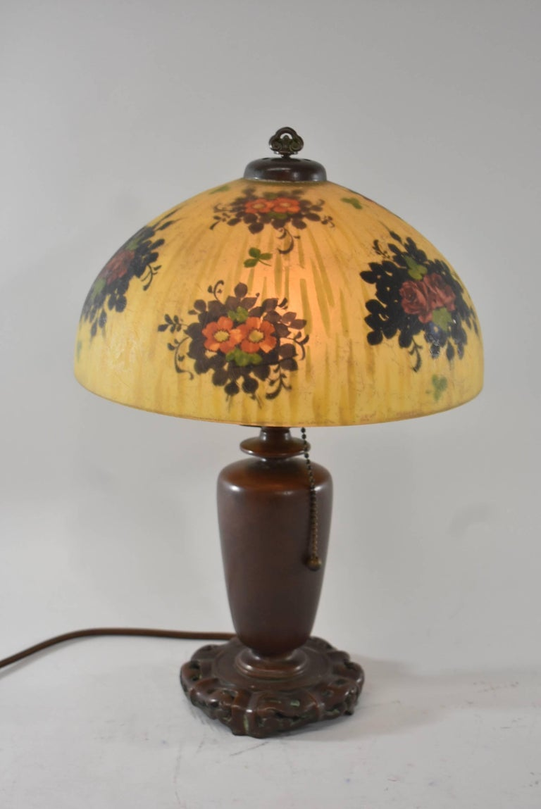 A beautiful boudoir lamp by Handel. It features a reverse painted shade with a glue chip exterior painted yellow with black, red roses, green foliage and purple violets. It has a Chinese base with a great patina, Hubell sockets, an acorn pull and a