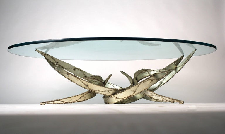 Silver leafed torch cut coffee table by Silas Seandel. Retains original glass top.   Base measures: 44 x 21