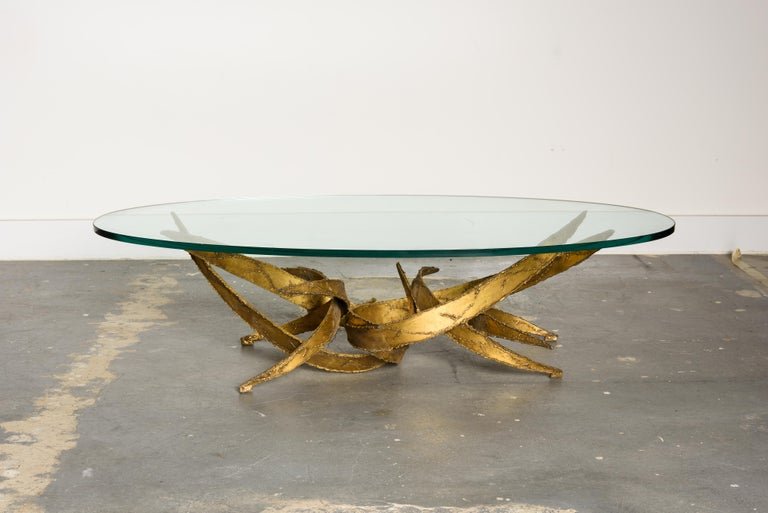 This sculptural Silas Seandel Brutalist coffee table is constructed of sections of curved gold tone torch cut metal which have been formed into an organically abstract structure and functional art piece. This structure balances a piece of glass to