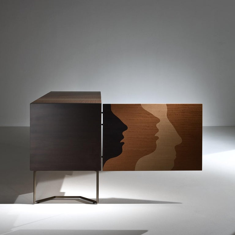This extraordinary wooden sideboard is an exclusive piece of exquisite craftsmanship, part of a limited series of only 21 specimens. The inlaid pattern on the surface uses different shades of wood to create a 3D arrangement of silhouettes. The two