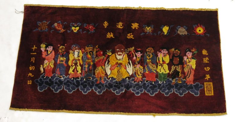 A Chinese silk pictorial rug. On a border-less burgundy red ground, 11 Immortals stand on clouds .Each immortal has its own unique colorful outfit or costume. The calligraphy most likely shows that it was woven somewhere in Beijing although we are