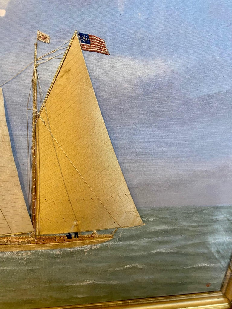 19th century silk embroidered and hand painted oil on canvas seascape by Thomas Willis (1850 - 1925), depicting a schooner-rigged racing yacht closely hauled on a starboard tack, flying the American Ensign and Burgee of the New York Yacht Club, two