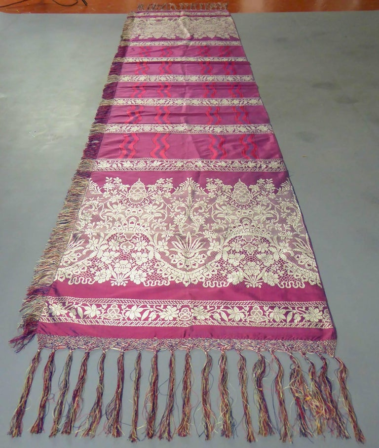 Circa 1860  France Lyon  A surprising woven stole with a lace decoration from an unidentified Lyonnais factory dating from the Second Empire. Silk lampas with silver plaited border and plum taffeta. Decor with ruffles of lace and ribbons of waving