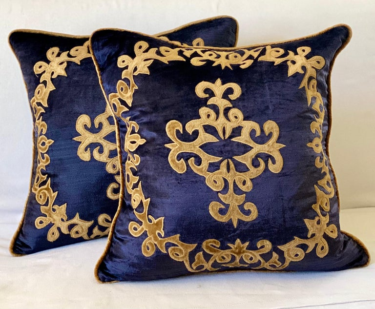 Semi antique silky velvet pillows with wonderful applique designs. The pillows are filled with down and Feathers, and close with a zipper.