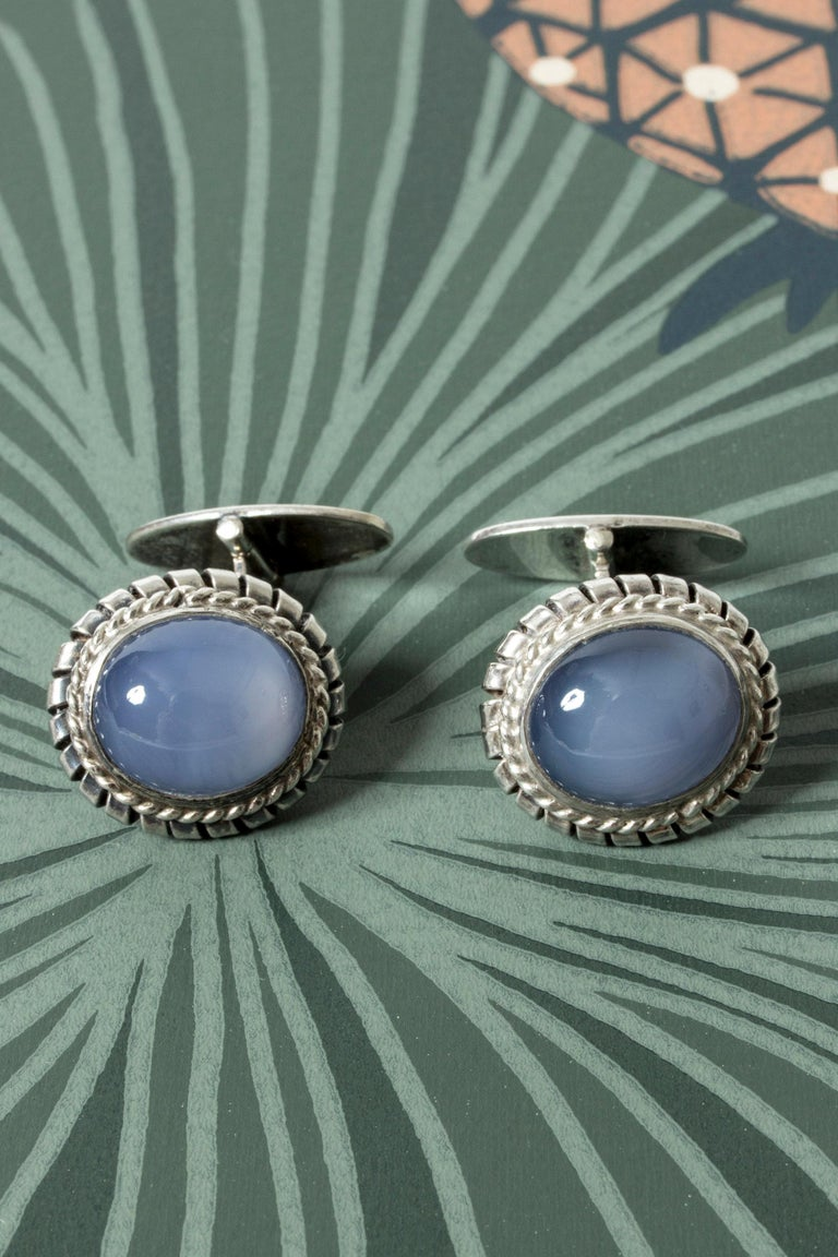 Pair of elegant silver cufflinks, with large, oval chalcedony stones. Ornate frames around the beautiful, sky blue stones.