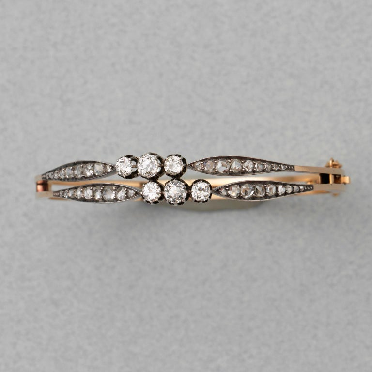 An 18 carat gold diamond bangle consisting of two bands each centering three old cut diamonds, the middle ons slightly bigger on both ends a navette shaped element set with rose cut diamonds all set in silver, France, circa 1880.  weighth: 16.97