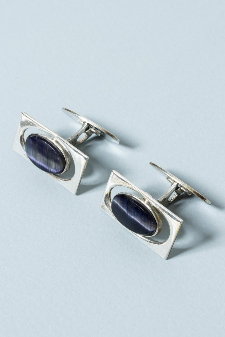 Pair of elegant silver cufflinks from Kaplans, with oval purple semiprecious stones in a cutout frame. Mesmerizing stones with a white sheen through the middle.