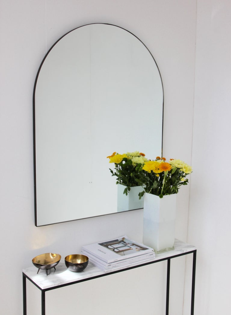 Delightful handcrafted large silver tinted arched mirror with a brass patinated frame.