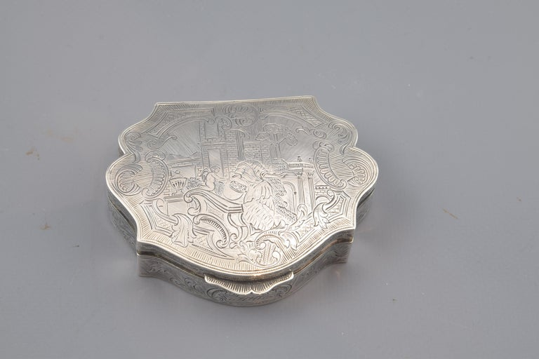 With hallmarks. Silver box in its color with flat top and side edges and lobed front, remembering, as does the decoration, the usual movement in the 18th century Rococo silverware. The cover has a frame of leaves, aveneradas forms and architectural